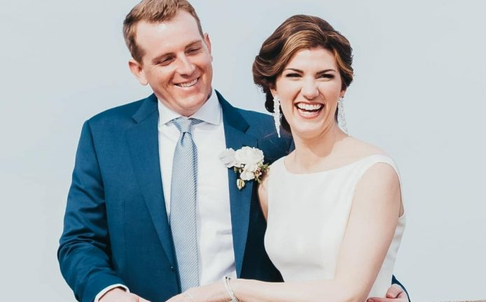 couple smiling on a dock at their waterfront wedding venues