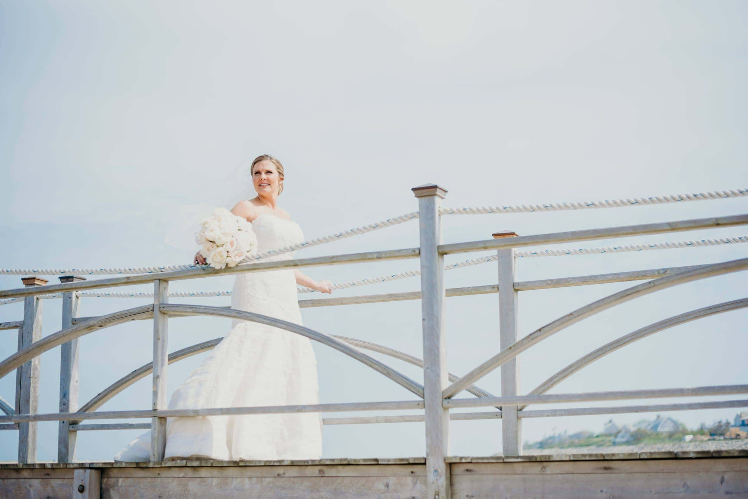 bride gazing out on dock at chatham bars inn waterfront wedding venue