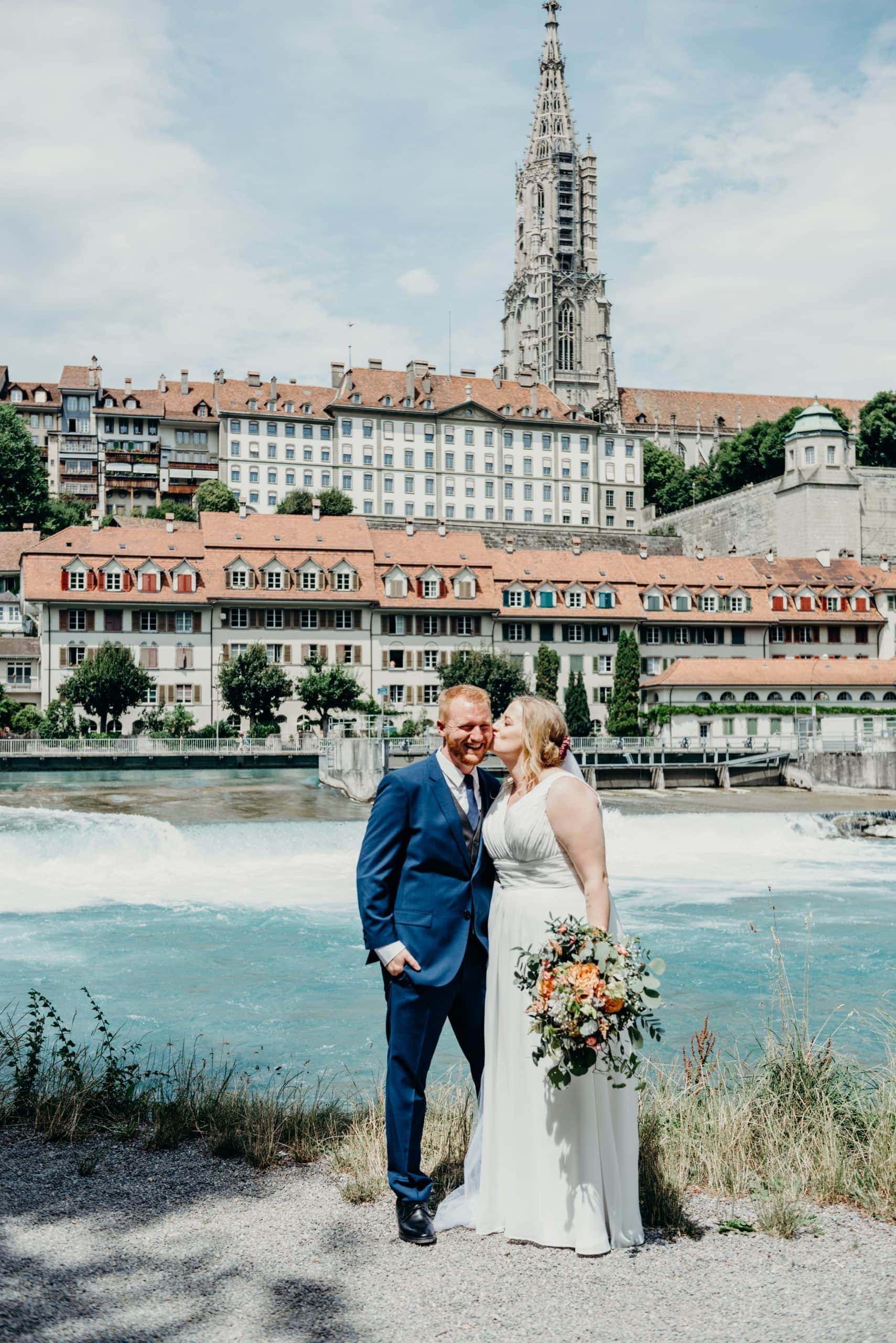 bride kissing groom's cheek in old town bern Switzerland for their Swiss wedding