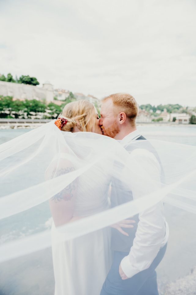 destination wedding Switzerland couple kissing veil blowing in old town bern Switzerland
