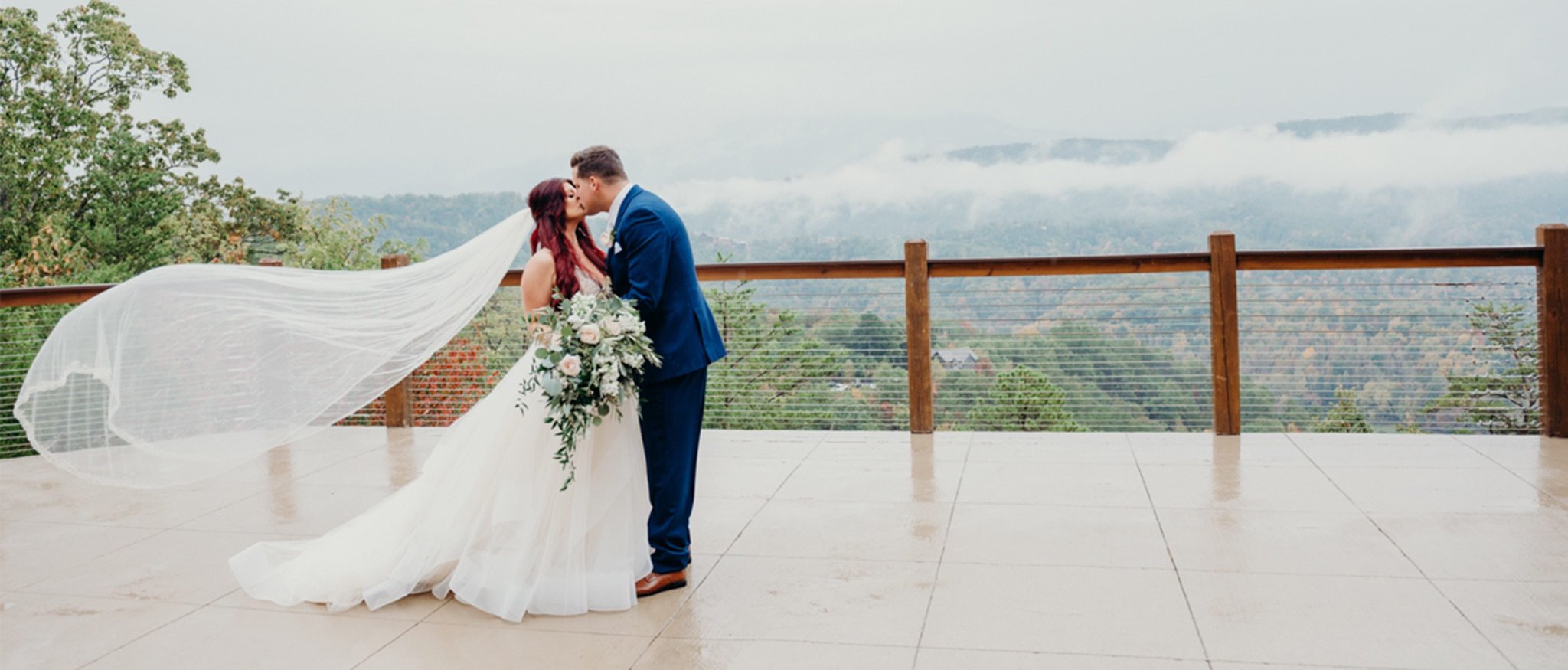 couple kissing with veil flying in the wind at the magnolia smoky mountain wedding venue in tennessee