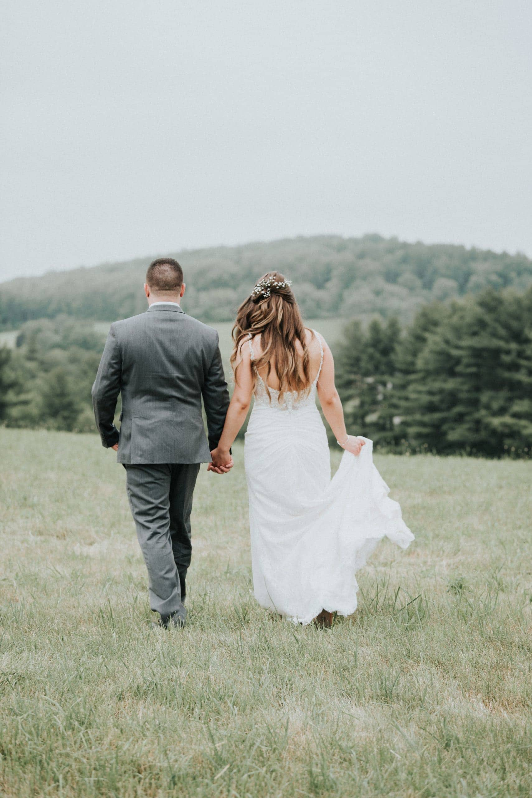 boho bride and groom walking away Zukas hilltop barn Spencer Massachusetts