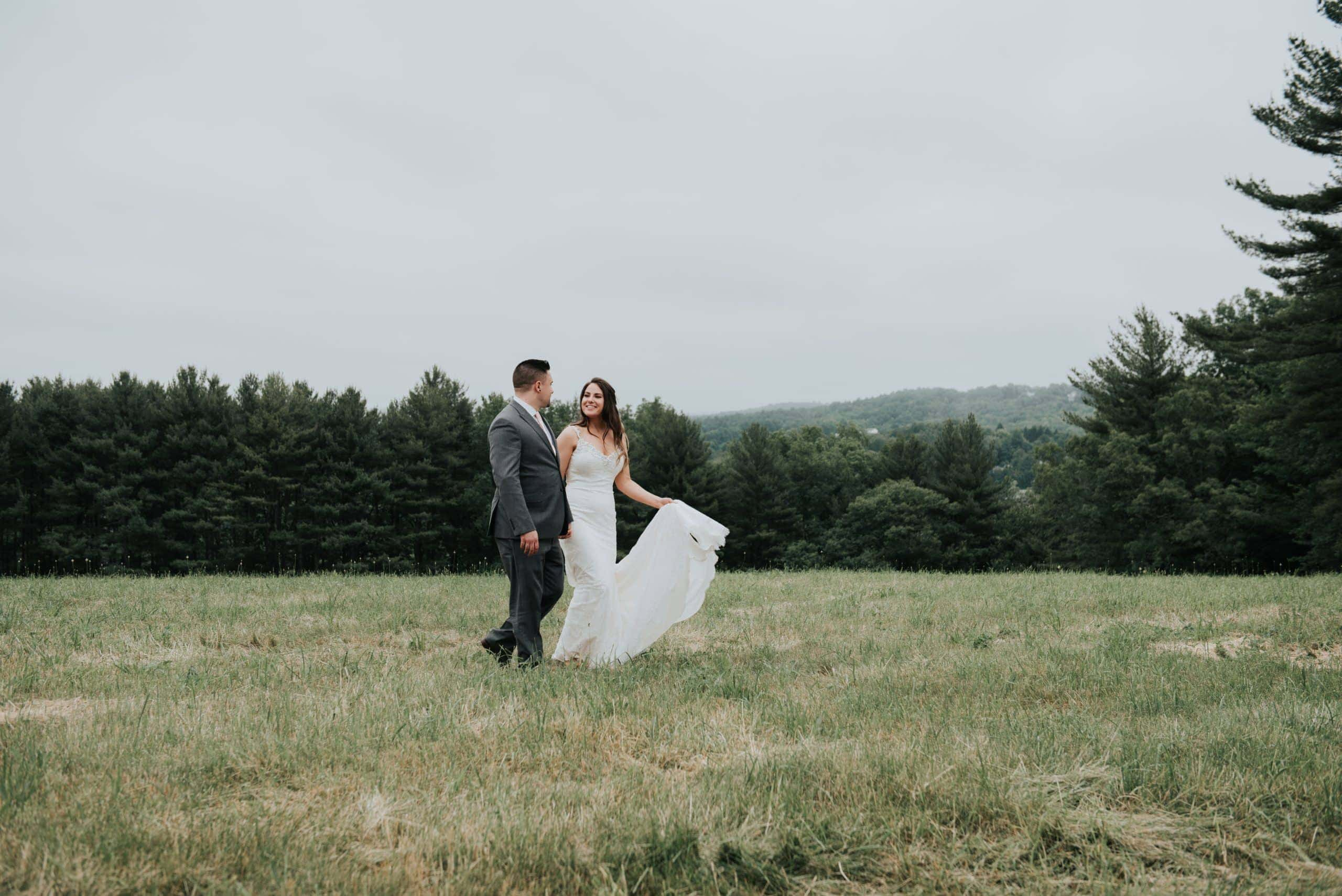 boho bride and groom walking in forest Zika's Hilltop Barn Wedding Spencer Massachusetts