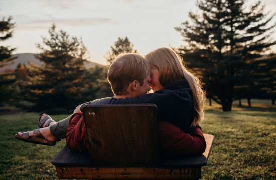sunsets over Vermont mountains as couple kisses in an Adirondack chair in their Ludlow backyard by vermont wedding photographer