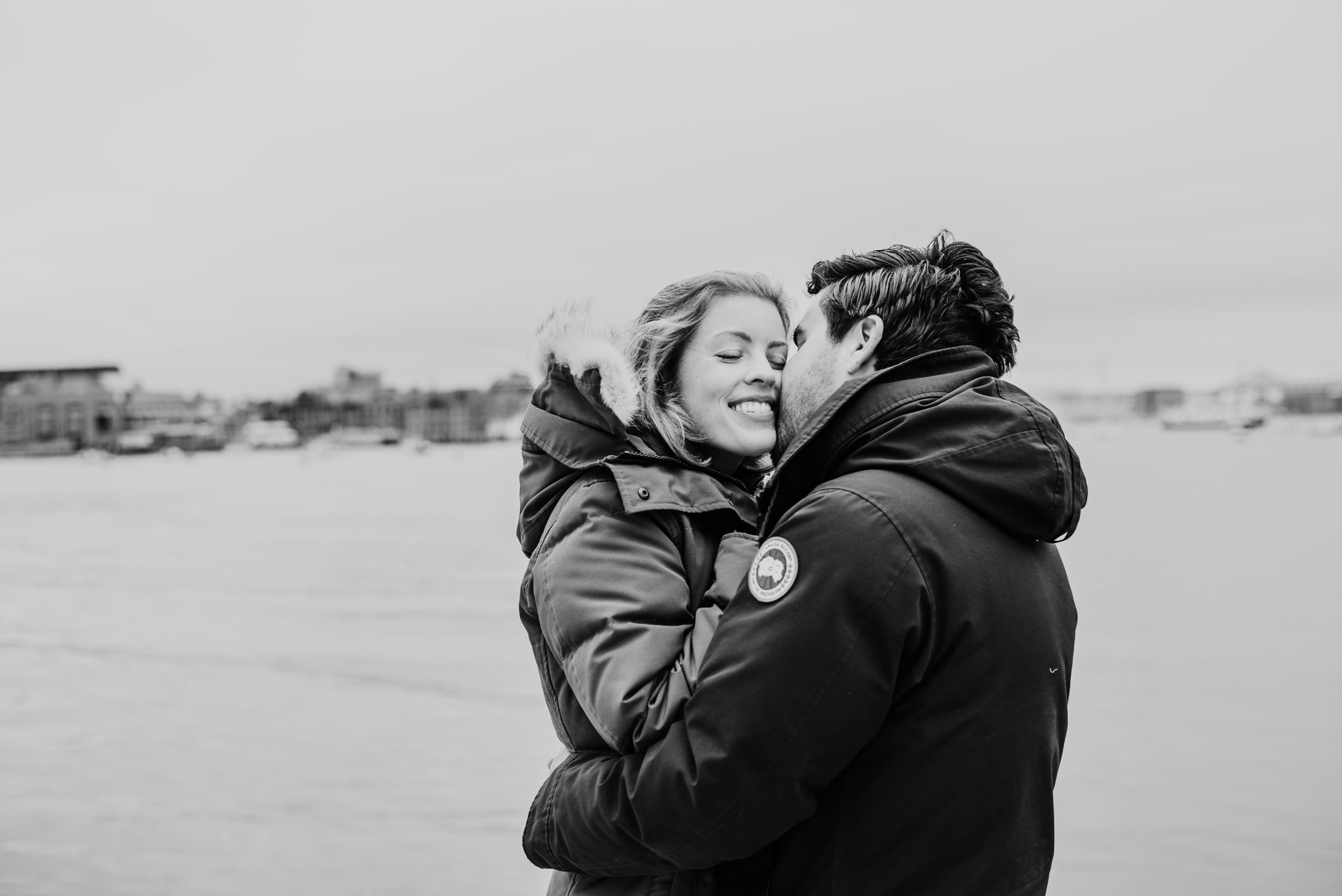 Couple kissing during winter engagement session in the Boston Seaport District at Fan Pier Park