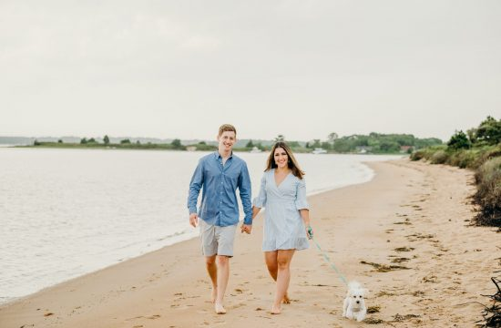 couple walking dog holding hands during their cape cod beach engagement session
