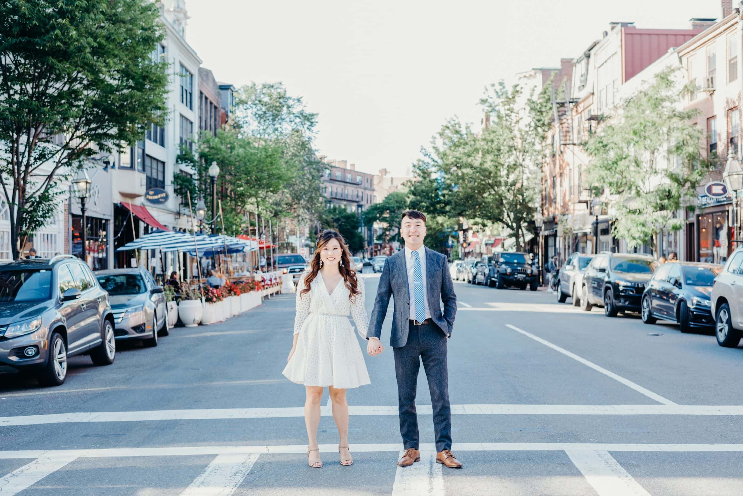 couple holding hands at crosswalk in beacon hill during their boston engagement session