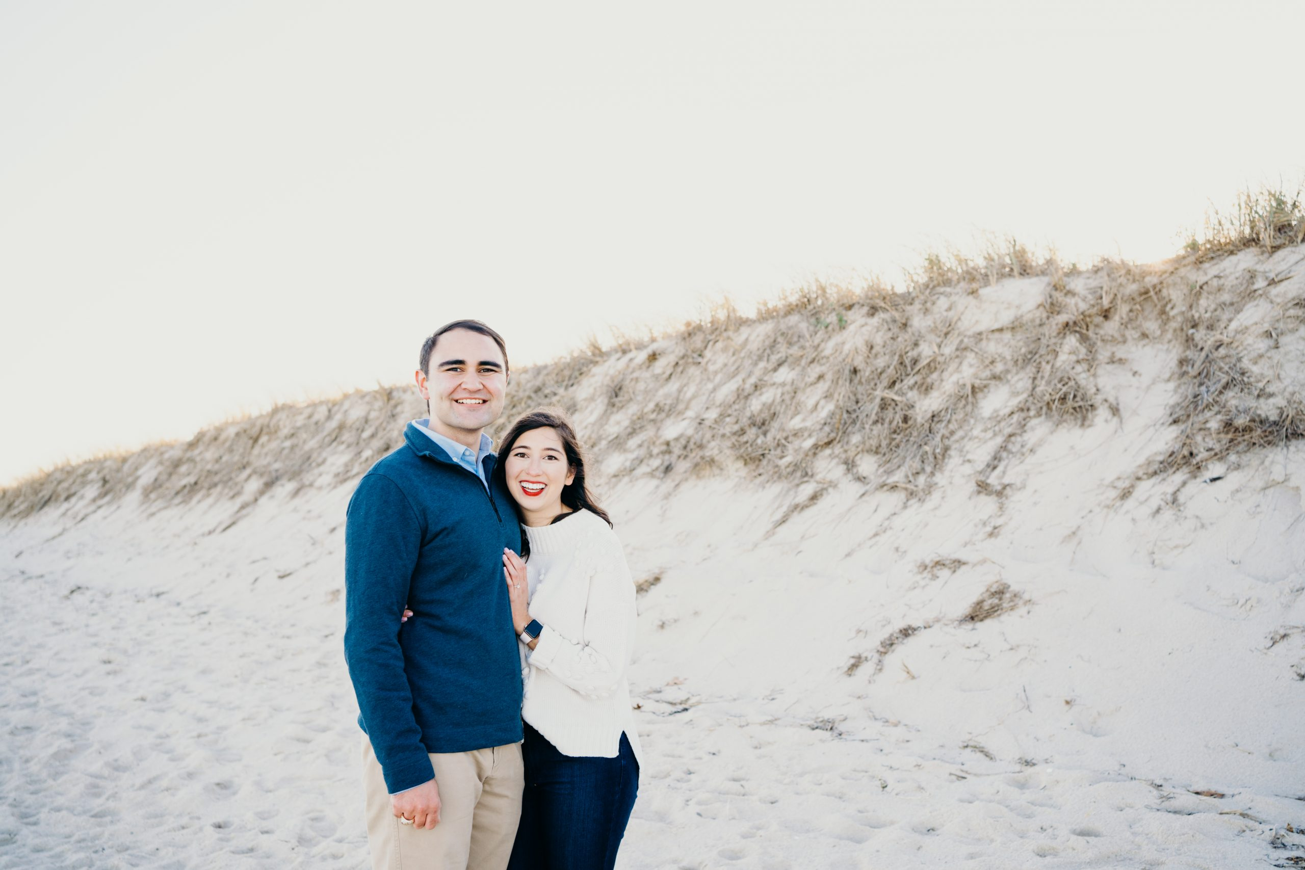 up close portrait of engaged couple in front of sand dunes during their cape cod couples session in chatham