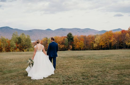 married couple walking towards green mountains in the distance at their mountain top inn wedding in chittenden vermont