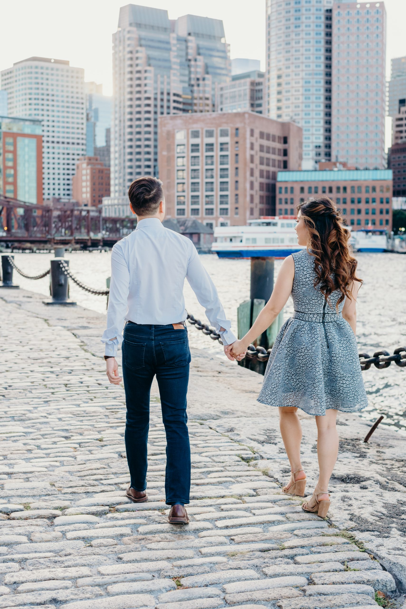 stylish engaged couple walking in the Boston seaport district's fan pier park towards the skyline