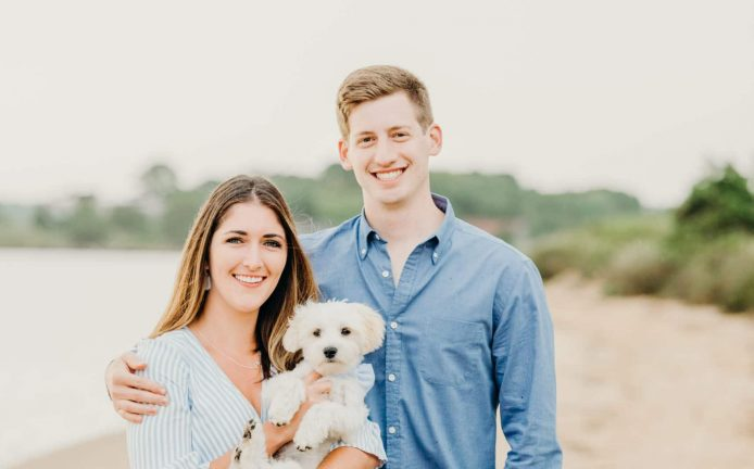 engaged couple smiling holding their dog on the beach during their Mashpee beach engagement session on cape cod massachusetts