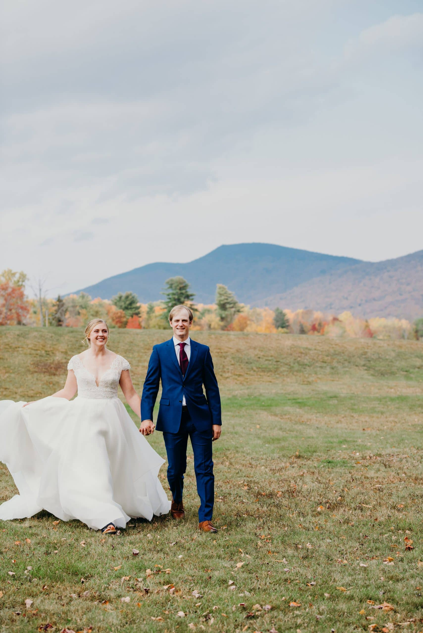 just married couple walking towards the camera during their luxurious wedding at the mountain top inn in Chittenden vermont
