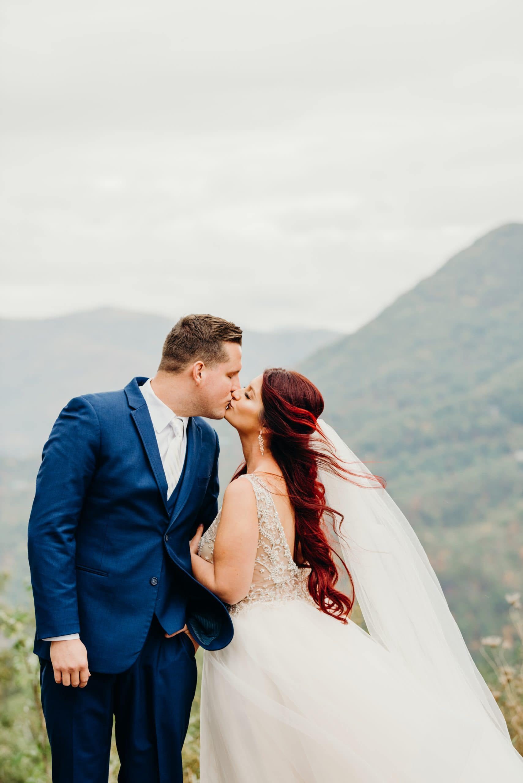 just married couple kissing in front of the smoky mountains during their magnolia venue tennessee wedding