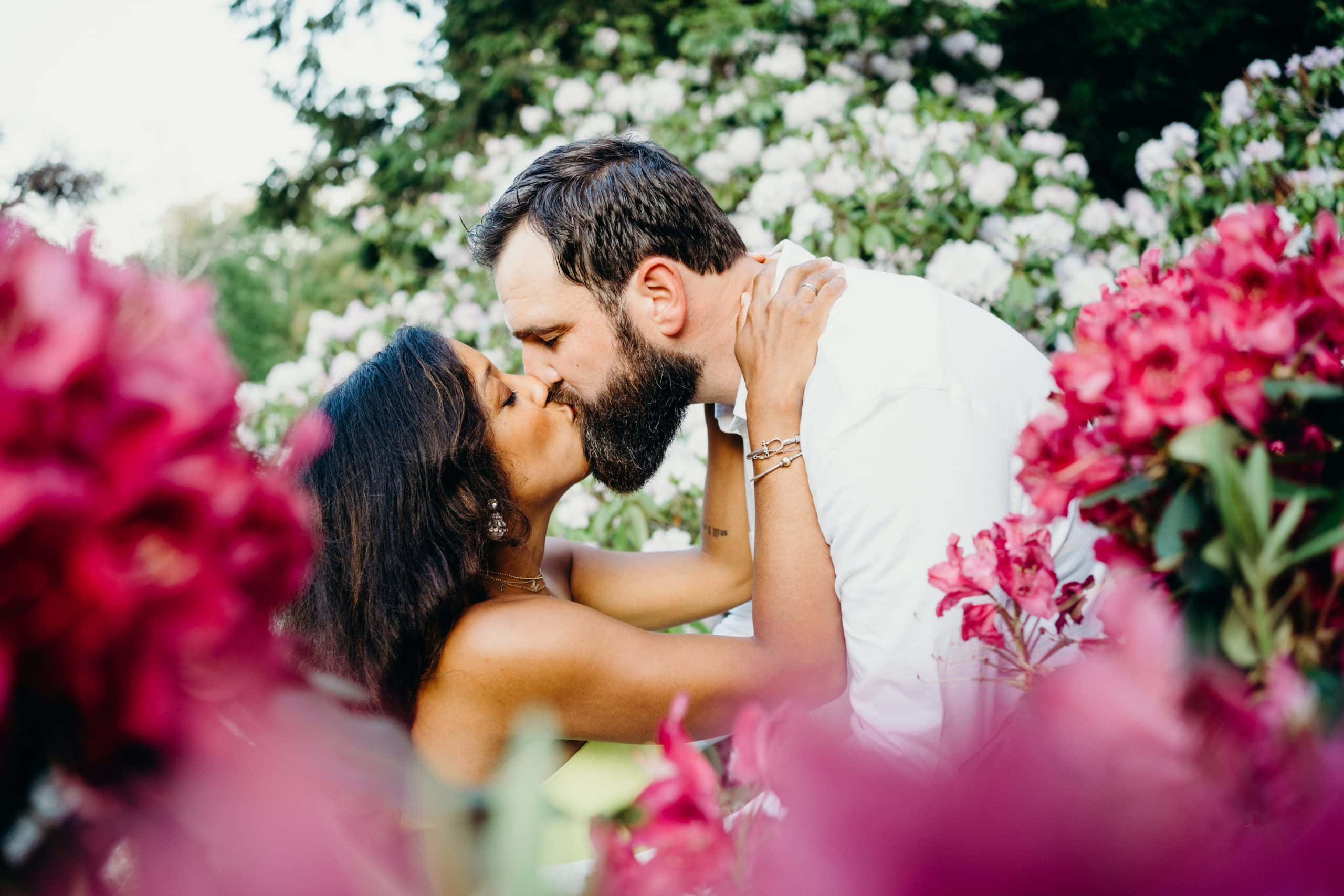 couple kissing surrounded by flowers during their Arnold Arboretum couples session in Jamaica Plain