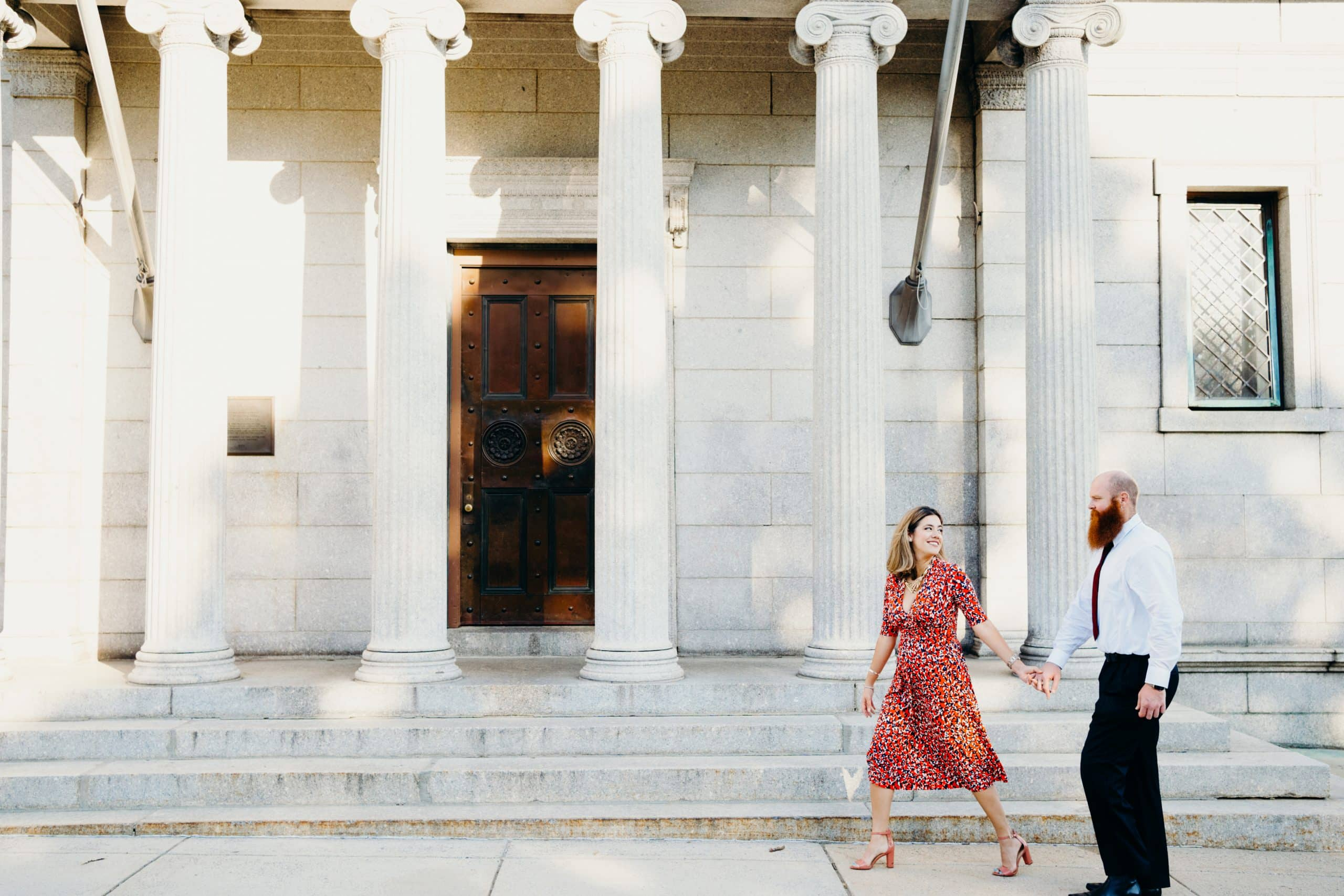 couple holding hands walking during their Charlestown bunker hill engagement session