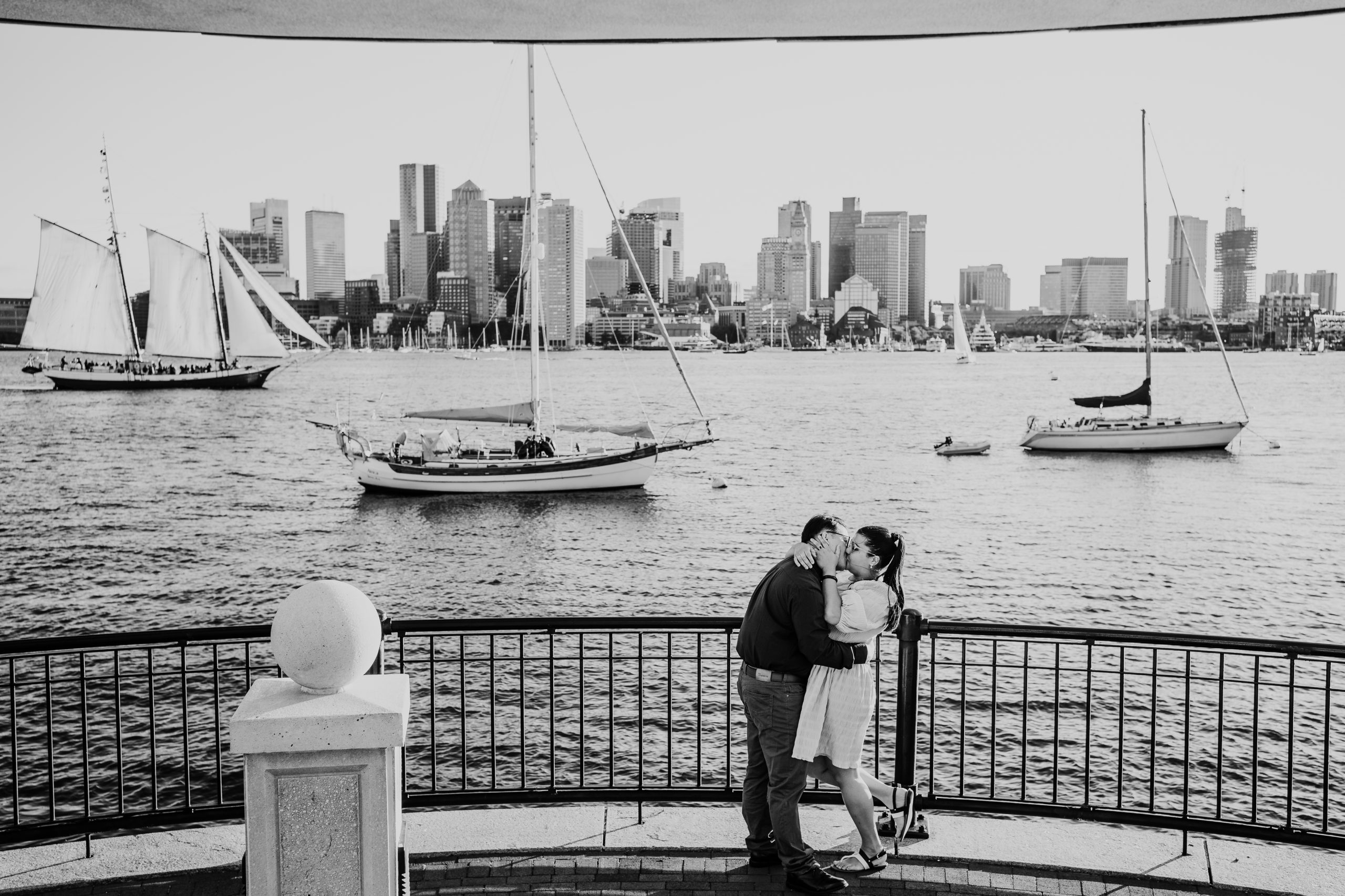black and white photo of couple kissing with the skyline view at piers park in East Boston during their couples session