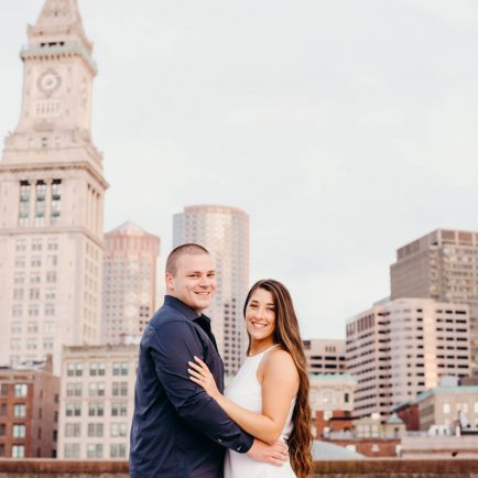 engaged couple smiling at camera with the city skyline behind them during their boston engagement session