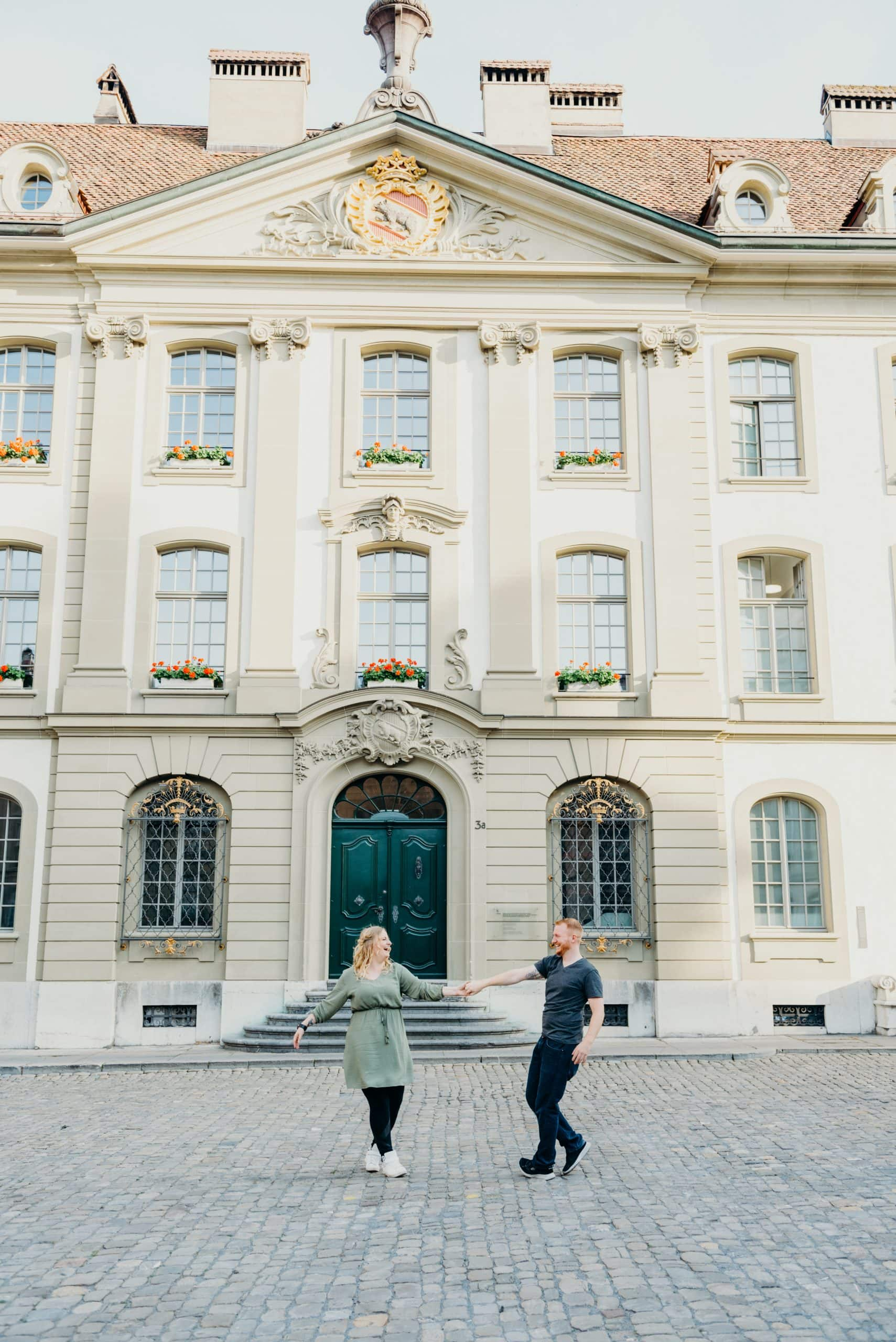 couple walking in front of Swiss building during their old town bern Switzerland engagement session