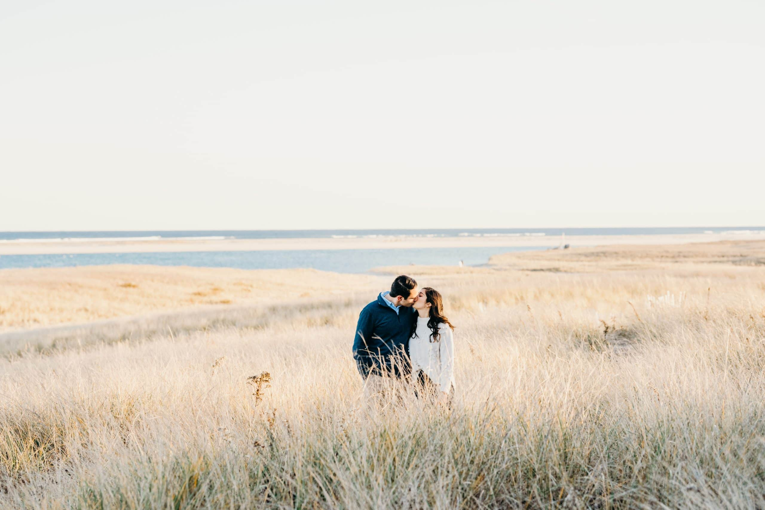 couple kissing in the dunes at the chatham lighthouse beach during their cape cod proposal