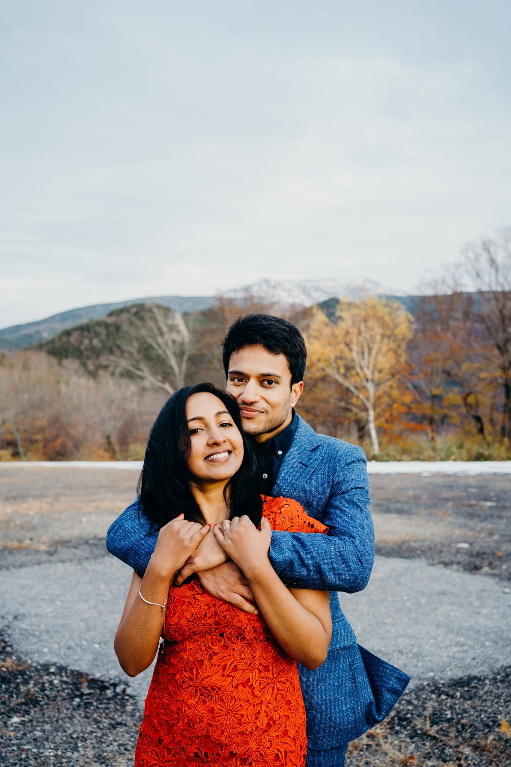 couple smiling at camera during their white mountains national forest engagement session in Franconia new hampshire
